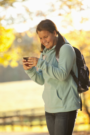 Caucasian teenager using cell phone outdoors