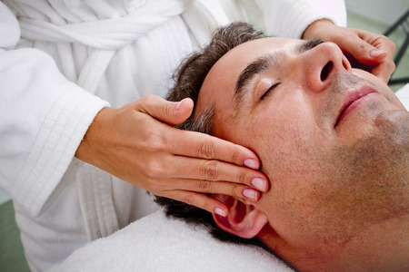 Hispanic man having face massage