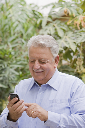 Senior Chilean man using cell phone