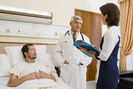 Doctor and nurse talking with patient in hospital room