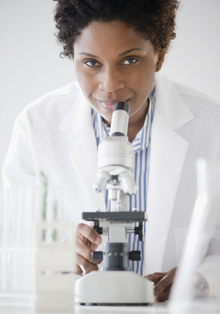 Black scientist standing with microscope
