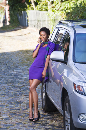 African American woman leaning against car talking on cell phone