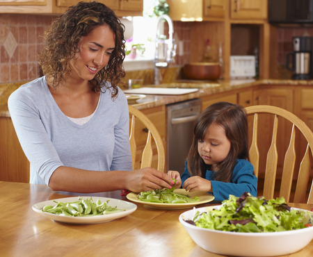 Mother and daughter shelling peas at dining table