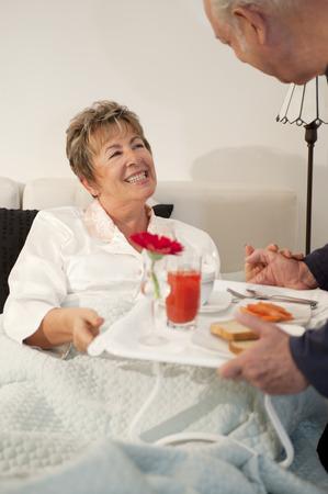 Senior Hispanic man bringing wife breakfast in bed Standard-Bild - 108054573