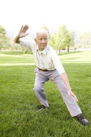 Senior Chinese man doing tai chi outdoors Stock Photo