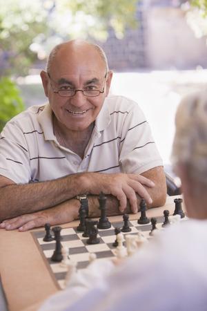 Senior men playing chess outdoors