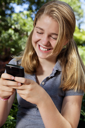 Caucasian girl text messaging on cell phone