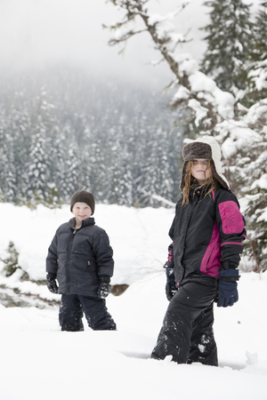 Caucasian children standing in snow