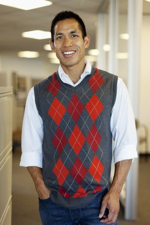 Smiling mixed race businessman standing in office