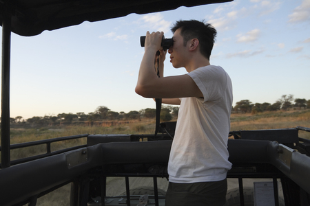 Chinese man riding in truck on safari using binoculars