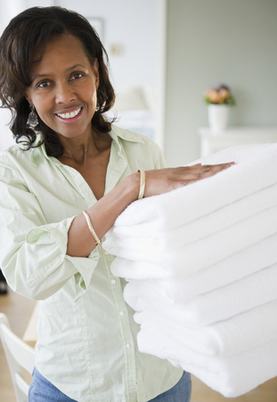 Black woman carrying stack of towels 写真素材