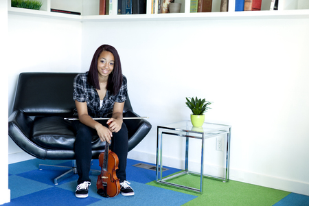 Mixed race girl sitting in chair with violin