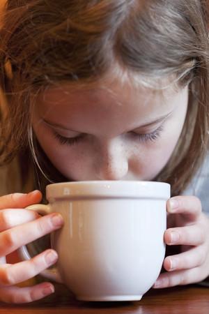 Caucasian girl drinking hot chocolate Stock Photo