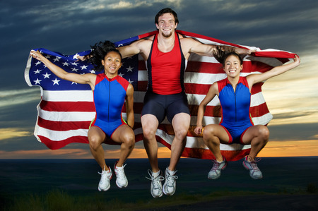 Athletes jumping in mid-air with American flag