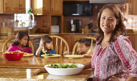 Mother serving salad to children Stock Photo