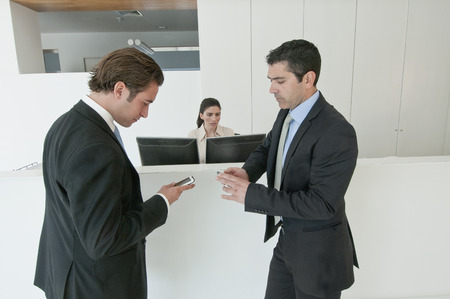 Hispanic businessmen holding cell phones in office Stock Photo