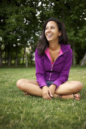 Smiling Hispanic woman sitting in park