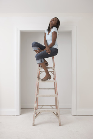 Black woman sitting on top of ladder