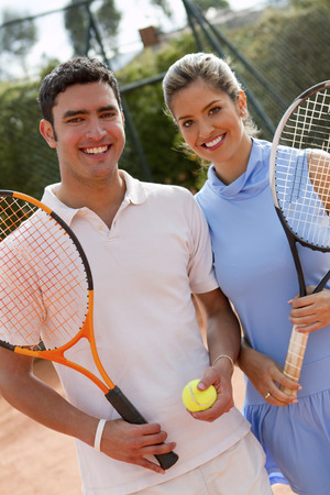 Hispanic couple standing on tennis court with racquet and ball Stock Photo