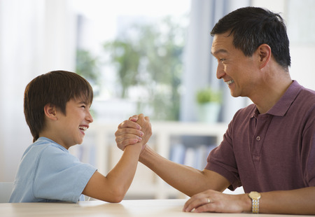 Smiling father and son arm wrestling at table Stock Photo