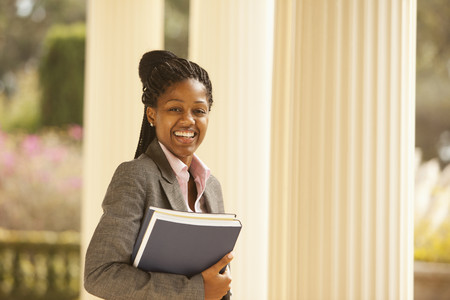 African American businesswoman holding paperwork outdoors