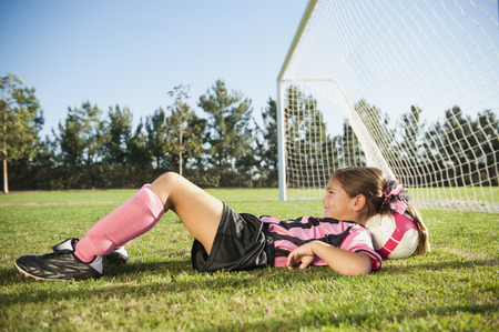 Hispanic girl soccer player laying with head on soccer ball