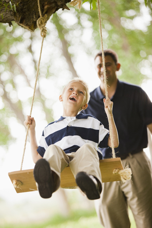 Caucasian father pushing son on swing 写真素材