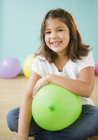 Smiling Hispanic girl holding balloon Stock fotó