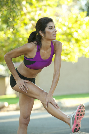 Hispanic woman in sportswear stretching in park