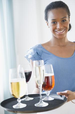 Black waitress carrying tray of drinks Reklamní fotografie