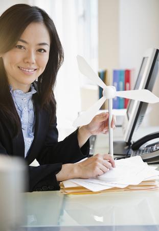 Japanese businesswoman holding model wind turbine Фото со стока