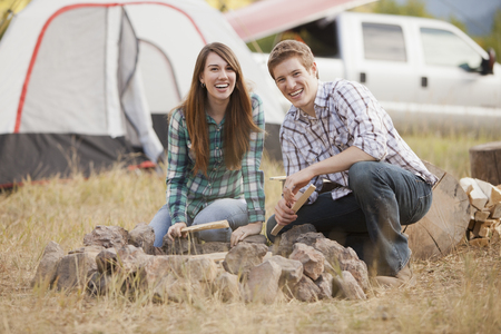 Caucasian couple building campfire at campsite Stock Photo