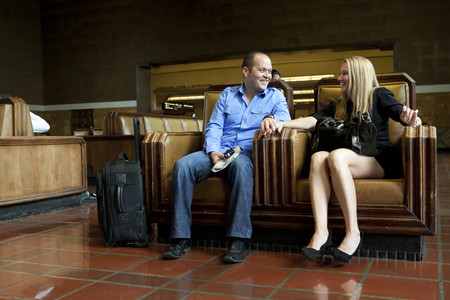 Couple sitting together in train station Stock Photo