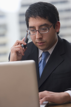 Chilean businessman using cell phone and laptop