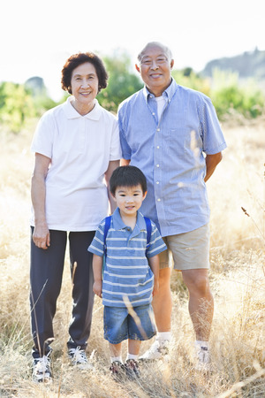 Chinese grandparents standing in field with grandson