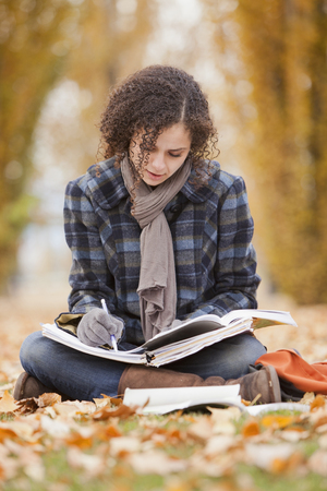 Caucasian woman doing home work in autumn leaves Imagens - 107933032