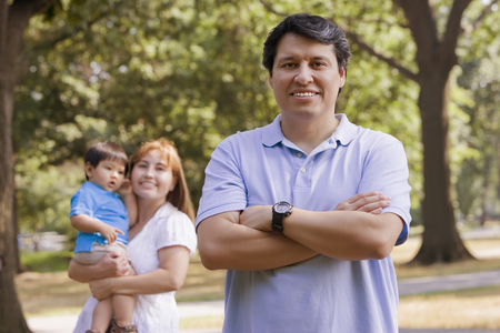 Smiling Hispanic man outdoors with family