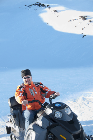 Hispanic man riding on snowmobile