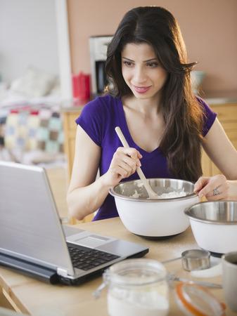 Mixed race woman baking and using laptop Stok Fotoğraf