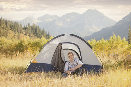 Caucasian man sitting in tent