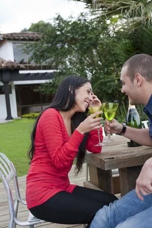 Hispanic couple drinking together outdoors