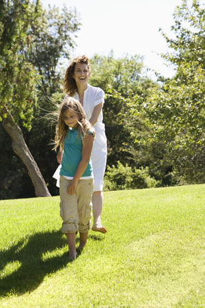 Smiling mother and daughter walking in grass together Stock Photo