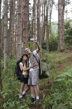 Hispanic couple hiking and taking photographs