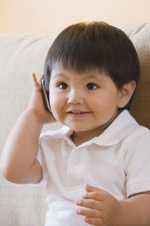 Hispanic baby boy using cell phone Stock Photo