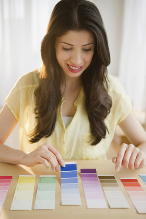 Mixed race woman looking at paint swatches Stock Photo