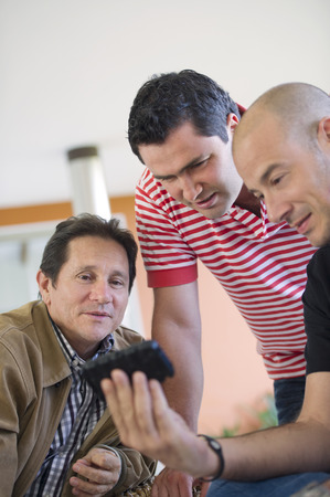 Hispanic friends looking at cell phone Stock Photo