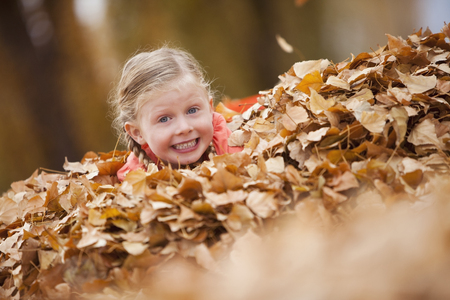 Caucasian girl playing in autumn leaves 写真素材