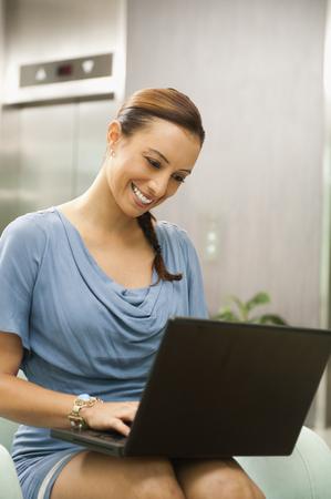 Hispanic businesswoman using laptop