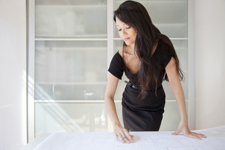 Mixed race businesswoman looking at blueprints in office