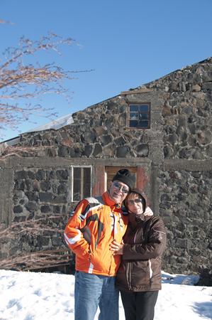 Hispanic couple standing in snow near house